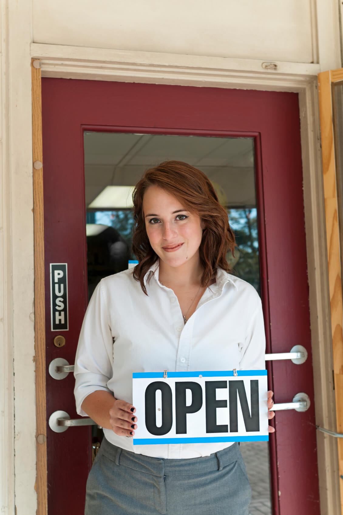 young woman standing in doorway of her newly opened small business